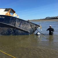Salvage experts attach lines cables to the beached fishing vessel Privateer they prepare to attempt moving the vessel further ashore to expedite salvage operations near Ocean Shores, Wash., May 10, 2016. (U.S. Coast Guard photo by Bradley Bennett)