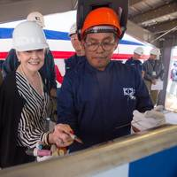 Ship Sponsor Kay Webber Cochran (center) sketches her initials onto the keel plate of the National Security Cutter Kimball (WMSL 756). Also pictured are her husband, Sen. Thad Cochran (left), R-Miss., and Ingalls Shipbuilding employee Jerry Wesley (right), who welded the initials onto the plate. Photo by Lance Davis/HII