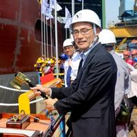 Takaaki Anraku, President Kokusai Cable Ship Company Ltd of Japan, cutting the rope to break the milk pot against the vessel's hull. Photo: Colombo Dockyard PLC
