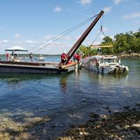 The Coast Guard oversees the removal of Stretch Duck 7 from Table Rock Lake in Branson, Missouri, July 23, 2018. Missouri State Highway Patrol divers rigged the vessel, then a barge crane lifted it to the surface before it was towed to shore and loaded onto a flatbed trailer for transport to a secure facility. (U.S. Coast Guard photo by Lora Ratliff)