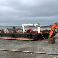 The Coast Guard responds to a fuel barge that settled in the mud and began to show signs of structural stress while offloading petroleum product on the Naknek River in Naknek, June 18, 2019. Coast Guard Marine Safety Task Force responders from Sector Anchorage and contracted cleanup professionals are standing by on site in the event that any fuel enters the water. U.S. Coast Guard photo
