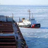 The crew of Coast Guard Cutter Neah Bay, homeported in Cleveland, works to keep the CSL Laurentien moving during an escort in eastern Lake Erie March 27, 2014. The crew experienced plate ice as thick as three feet and ice ridges as tall as eight feet. (U.S. Coast Guard photo courtesy of CSL Laurentien)