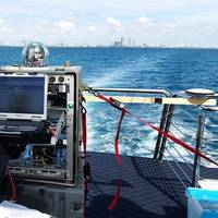 The TREC test assembly shown on the charter vessel as it enters the Port of Miami. Researchers established communications links with a similar terminal located on the roof of one of the buildings in the distance. (Photo: U.S. Naval Research Laboratory)