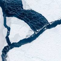 The wind has opened a lead between ice floes. As the white streaks reveal, the water surface is freezing again immediately. The streaks occur when the wind drifts loose ice crystals. Photo IceCamStefan Hendricks, Alfred-Weg