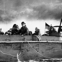 "Troops and crewmen aboard a Coast Guard manned LCVP as it approaches a Normandy beach on ""D-Day"", June 6, 1944. (Photograph from the U.S. Coast Guard Collection in the U.S. National Archives.)"