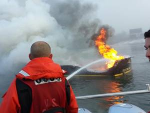 Coast Guard Petty Officer 3rd Class Cory Langston fights the boat fire from the Coast Guard 29-foot response boat in Hopkins Point Marina in Jonesport, Maine on Thursday, Sept. 8, 2016. The was no one aboard at the time of the fire. (U.S. Coast Guard photo by Stephanie Horvat)