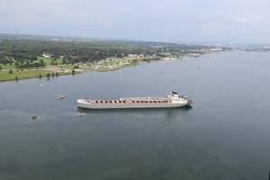 The 629-foot cargo vessel Calumet sits hard aground in the St. Marys River southeast of Sault Ste. Marie, Michigan, while a Coast Guard response boat - medium encircles the vessel, August 10, 2017. The vessel was heading to its next port of call in Brevort, Michigan when it ran aground. (US Coast Guard photo)