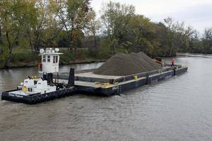 After an area has been dredged of contaminated sediment to the EPAs standards, clean backfill is transported on a barge by a tug boat. The backfill replaces dredged sediment and maintains the natural contours of the riverbed. (Photo: EPA)