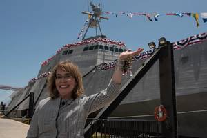 Former U.S. Rep. Gabrielle Gabby Giffords waves to a crowd in front of the littoral combat ship, USS Gabrielle Giffords (LCS 10). (Photo courtesy Austal USA/Released)
