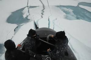Sailors aboard the fast attack submarine USS Seawolf (SSN 21) inspect the boat after surfacing through Arctic ice. Seawolf conducted routine Arctic operations. (U.S. Navy photo/Released)