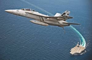 An F/A-18F Super Hornet assigned to Air Test and Evaluation Squadron (VX) 23 flies over USS Gerald R. Ford (CVN 78). The aircraft carrier is underway conducting test and evaluation operations. (U.S. Navy photo by Erik Hildebrandt)