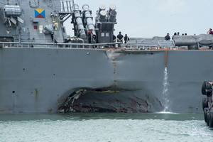 Damage to the portside is visible as the USS John S. McCain steers toward Changi Naval Base, Singapore, following a collision with the merchant vessel Alnic MC while underway east of the Straits of Malacca and Singapore. Significant damage to the hull resulted in flooding to nearby compartments, including crew berthing, machinery and communications rooms. (U.S. Navy photo by Joshua Fulton)