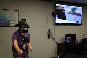 Computer Engineer Daniel Stith shows how to use the hands-free headset for the virtual reality simulation. (Photo: U.S. Navy)