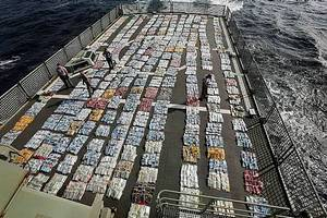Members of HMAS Toowoomba account for and weigh 5.6 tonnes of cannabis resin on the flight deck of HMAS Toowoomba during Operation Manitou. Photo: James Whittle