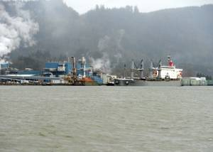 Two tugs support Sparna past the Wauna Paper Mill while in transit along the Columbia River to their mooring destination in Kalama, Wash., March 23, 2016. (U.S. Coast Guard photo by Levi Read)