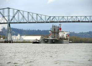 A pair of tugs support the 623-foot motor vessel Sparna under the Lewis and Clark Bridge while transiting to a pier in Kalama,Wash., March 23, 2016. A small boat crew from Coast Guard Station Portland also escorted the Sparna enforcing a 100-yard safety zone. (U.S. Coast Guard photo by Levi Read.)