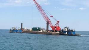The vessel Kimberly Selvick (left), connected to a crane barge, is pushed by a tug through Lake Michigan after being salvaged from the shores of Lake Michigan near Burnham Park outside of Chicago, May 10, 2014. The Kimberly Selvick became partially submerged after taking on water May 5. (U.S. Coast Guard photo by Lt. Heidi Braglone)