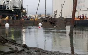 The tug Respect is hauled to the surface of the Oakland Estuary Wednesday, Dec. 18, 2013. The tug, which sank at its moorings in 2007, will be transported to a nearby yard for scrapping. Coast Guard photo by Thomas McKenzie
