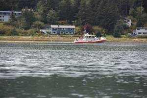 A Coast Guard Station Juneau 45-foot Response Boat-Medium crew and members of the Sector Juneau response department deploy containment boom around the sunken tug Challenger in Gastineau Channel in Juneau, Alaska, Sept. 13, 2015. The vessel sunk the day before while anchored in the channel. (U.S. Coast Guard photo by Petty Officer 2nd Class Grant DeVuyst)