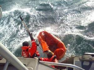 Coast Guard crewmembers use a boat hook to pull in a empty life raft after rescuing a man who abandoned his sinking sailing vessel ( U.S. Coast Guard photo by Seaman Alyssa Petty)
