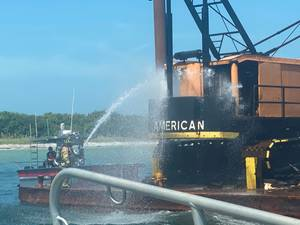 A West Manatee County Fire Department marine unit crew extinguish the fire on a commercial barge after a good Samaritan reported the incident. (U.S. Coast Guard photo)