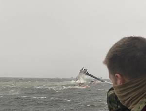 The crew of the Coast Guard Cutter Glenn Harris pulls a person from the water April 13, 2021 after a 175-foot commercial lift boat Seacro Power capsized 8 miles south of Port Fourchon, LA. (U.S. Coast Guard photo courtesy of Coast Guard Cutter Glenn Harris)