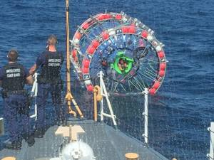 The crew of the Coast Guard Cutter Gannet speak with a man within a hydro pod off the coast of Jupiter, Florida, April 24, 2016. After speaking with the crew aboard the Gannet, Reza Baluchi agreed to end his voyage Bermuda and safely embarked the cutter. (U.S. Coast Guard photo)