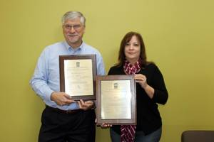 Tom Johnson, President, and Merralee Burr, HS&E Management Representative, hold BMT Scientific Marine Services plaques for ISO 14001:2004 and OHSAS 18001:2007 certification.