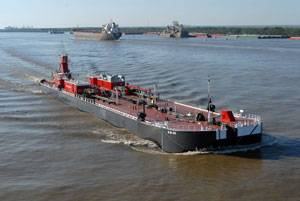 Bouchard's B. No. 262 and tug Evening Tide navigate down the Mississippi River delivering the barge's first load of cargo.  B. No. 262 was built and delivered from Bollinger Marine Fabricators.