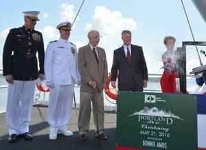 Ship Sponsor Bonnie Amos christens Portland (LPD 27), accompanied by (left to right) U.S. Marine Corps Maj. Gen. Christopher Owens, director of the U.S. Navy's expeditionary warfare division; Capt. Jeremy Hill, prospective commanding officer, Portland; Ted Waller, a World War II veteran who served on the first USS Portland (CA 33); and Brian Cuccias, president of Ingalls Shipbuilding. Portland is the 11th LPD to be built by Ingalls. (Photo by Lance Davis/HII)