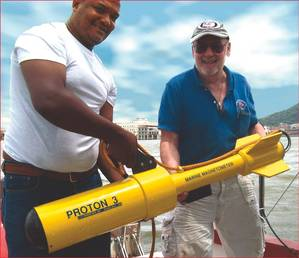 Russell Bennett (r) prepares to survey for shipwreck sites in Panama's old harbor area with his JW Fishers Proton magnetometer. Presidential Palace is visible in the background between the two men.