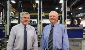 Bill Heller (left), new President and CEO of Messer Cutting Systems; and retiring President and CEO Gary Norville. In the Background is Messer's Titan III Cutting Machine