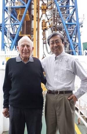 JAMSTEC President Asahiko Taira with Walter Munk on the deck of D/V Chikyu in front of the ships drilling derrick. Credit: JAMSTEC