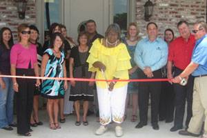 From left to right: Bridget Patterson, Catina Guidry, Candace Landry, Michelle Breaux, Edna D. Lopez, Sarah Schultz, Mona Delcambre, Ed Schultz, Selina Henry (cutting the ribbon), Sara Faulk, Jason Bergeron, Sheila Peckinpaugh, Charlie Hardy, Gerald Faulk