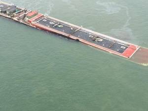 The partially submerged barge: Photo credit USCG