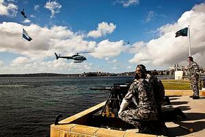 The Royal Australian Navys Three Pound Saluting Gun Battery prepares to fire across Sydney Harbour as a Squirrel Helicopter decorated with International Fleet Review decals hovers off Garden Island Naval Base as a Seahawk helicopter flying a giant International Fleet Review Flag flys past.