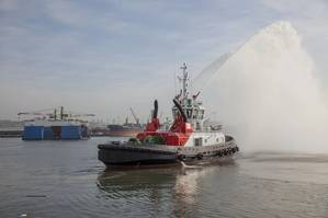 A tug spray from the Port of Durban's new UMBILO tug while the Port of Richards Bay's Usiba tug is lowered into the water in the background. (Photo: TNPA)