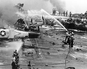 Crew members fight a series of fires and explosions on the carrier USS Forrestals after flight deck, in the Gulf of Tonkin, 29 July 1967. The conflagration took place as heavily-armed and fueled aircraft were being prepared for combat missions over North Vietnam. (Official U.S. Navy Photograph.)