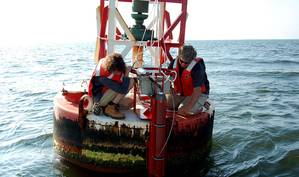Max Ivanov and Scott Mowery with NOAAs Center for Operational Oceanographic Products and Services install an improved current sensor system on a navigation buoy in Chesapeake Bay. The system transmits real-time current speed and direction observations via satellite to help mariners more safely navigate busy shipping channels. (Photo: NOAA)
