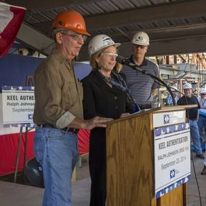 "With Ingalls Shipbuilding President Brian Cuccias (right) observing, shipfitter Bob Boegner (left) and Ship Sponsor Georgeann McRaven delcare the keel of Ralph Johnson (DDG 114) to be ""truly and fairly laid."" Photo by Lance Davis/HII"