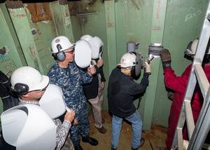 David Bazemore welds a ceremonial plate into the new mast on the aircraft carrier USS Abraham Lincoln (CVN 72). Also pictured (left to right) are Capt. Ronald L. Ravelo, incoming commanding officer, CVN 72; Ken Mahler, Newport News vice president, Navy Programs; Capt. Karl O. Thomas, outgoing commanding officer, CVN 72; Bruce Easterson, program director, CVN 72 RCOH; and Newport News shipbuilder Leary Putrell. Photo by Chris Oxley/HII