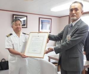 Captain Gaku Hinata (left) receives the certificate of commendation from MOL Managing Executive Officer Takaaki Inoue.