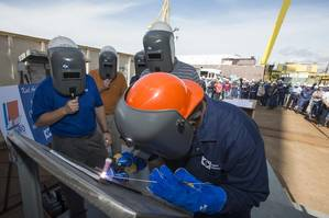 Roderick P. Funches, a structural welder at Ingalls Shipbuilding, welds the initials of Julie Sheehan on a ceremonial keel plate that will be welded to WMSL 755, the National Security Cutter named in honor of her great uncle, Douglas A. Munro. Photo by Andrew Young/HII