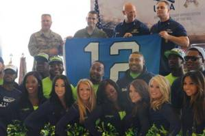 Master Chief Petty Officer Charles Lindsey (top right), command master chief of the Coast Guard 13th District, and Rear Adm. Richard Gromlich, commander of the Coast Guard 13th District, accept a Seattle Seahawks 12th Man flag from the Air Force 446th Airlift Wing (USCG photo by Katelyn Shearer)