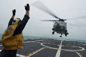Boatswains Mate 2nd Class Adam Garnett signals an MH-60R Sea Hawk helicopter from Helicopter Maritime Strike Squadron (HSM) 35 on the flight deck of the littoral combat ship USS Fort Worth (LCS 3). Fort Worth is currently on station conducting helicopter search and recovery operations as part of the Indonesian-led efforts to locate missing AirAsia Flight QZ8501. (U.S. Navy photo by Antonio P. Turretto Ramos)