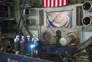 A welder carves the initials of ships sponsor Diane Donald on a metal plate during the keel laying ceremony for the future Virginia-class attack submarine Indiana (SSN 789). (U.S. Navy photo courtesy of Huntington Ingalls Industries by Ricky Thompson)