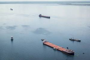 Two freighters transit upbound the Soo Locks past the safety zone established by the U.S. Coast Guard around the motor vessel Roger Blough near Gros Cap Reefs Light, May 30, 2016 in Lake Superior. (U.S. Coast Guard photo by Christopher M. Yaw)