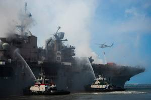 A helicopter provides aerial firefighting support alongside sailors and civilian fire crews on the ground to fight the fire aboard amphibious assault ship USS Bonhomme Richard (LHD 6). (U.S. Navy photo by Mar'Queon A. D. Tramble)