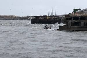 The semi-submerged tugboat Miss Bonnie sits in the water after alliding with the Old Bonner Bridge in Oregon Inlet, North Carolina. (U.S. Coast Guard photo courtesy of Coast Guard Station Oregon Inlet)