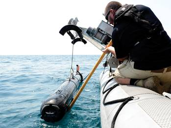 File A civilian contractor steadies a M18 Mod 2  Kingfish Unmanned  Underwater Vehicle (UUV) as it is lifted with a crane onto the deck of an  11-meter rigid-hull  inflatable boat.  (U.S. Navy photo by Mass Communication Specialist 2nd Class Blake Midnight/Released)